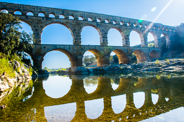 Roman aqueduct with reflection in the Gardon River, France.
