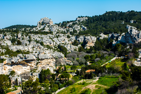 A valley in Les Baux, France surrounded by limestone hills.