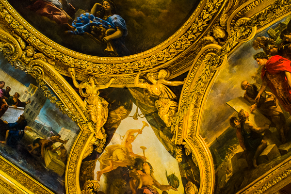 Ceiling corner of a room with statuesque figures as well as paintings in the Versailles Palace, France..