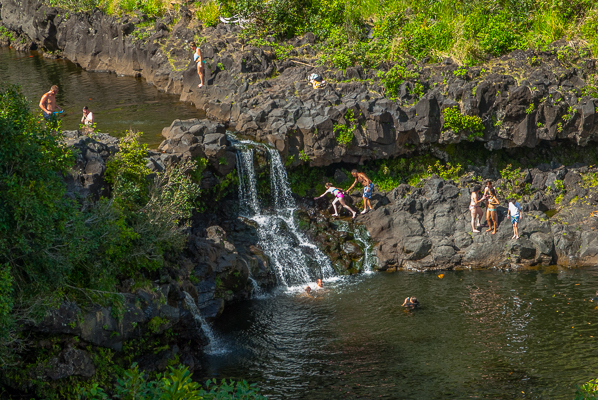 Swimmers and waterfall at Haleakalā National Park, Kipahulu on the Road to Hana in Maui.